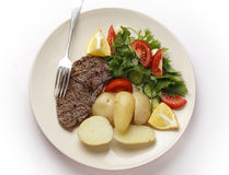 Minute steak meal from above. Pan-grilled pepper minute steak served with a salad of fresh leaves, tomato, cucumber and lemon with boiled new potatoes Stock Photos