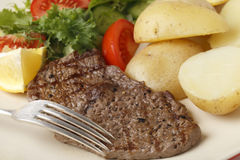 Minute steak meal closeup with fork. Pan-grilled pepper minute steak served with a salad of fresh leaves, tomato, cucumber and lemon with boiled new potatoes Stock Photos