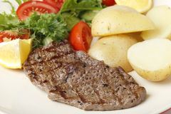 Minute steak meal. Pan-grilled pepper minute steak served with a salad of fresh leaves, tomato, cucumber and lemon with boiled new potatoes stock image