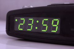 Minute to midnight. Digital tabletop clock showing one minute to midnight 23.59 royalty free stock photos
