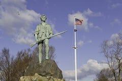 Minuteman-Statue und US-Markierungsfahne Stockfotografie