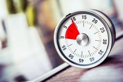 10 Minuten - analoger Küchen-Timer auf Countertop nahe bei Cooktop Stockfotografie