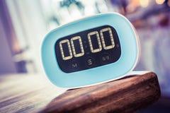 0 Minuten - blauer Küchen-Timer Digital auf Rand des Holztischs Stockfotos