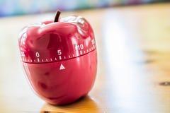 5 Minuten - Küchen-Eieruhr in Apple-Form auf Holztisch Lizenzfreie Stockfotografie