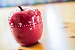 30 Minuten - Küchen-Eieruhr in Apple-Form auf Holztisch Lizenzfreie Stockbilder