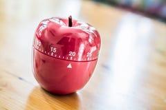 20 Minuten - Küchen-Eieruhr in Apple-Form auf Holztisch Stockbild