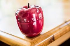 50 Minuten - Küchen-Eieruhr in Apple-Form auf Holztisch Lizenzfreie Stockfotos