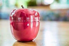 25 Minuten - Küchen-Eieruhr in Apple-Form auf Holztisch Lizenzfreies Stockbild
