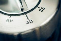 40 Minuten - Makro eines analogen Chrome-Küchen-Timers auf hölzerner T Stockfotos