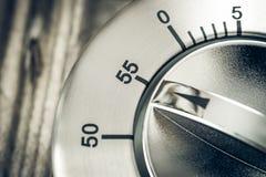 55 Minuten - Makro eines analogen Chrome-Küchen-Timers auf hölzerner T Lizenzfreies Stockfoto