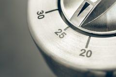 25 Minuten - Makro eines analogen Chrome-Küchen-Timers auf Holztisch Stockbilder