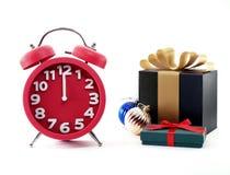 Minuten vor neuem Jahr, roter Uhr, Geschenkboxen und Weihnachtsbällen Lizenzfreie Stockfotos