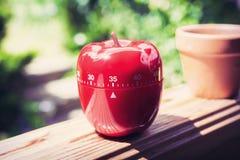 Minuterie minute d'oeufs de la cuisine 35 dans la forme d'Apple se tenant sur une balustrade Photo libre de droits