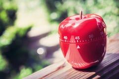 Minuterie minute d'oeufs de la cuisine 45 dans la forme d'Apple se tenant sur une balustrade Photos stock
