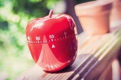Minuterie minute d'oeufs de la cuisine 55 dans la forme d'Apple se tenant sur une balustrade Photographie stock