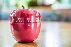 25 minutes - minuterie d'oeufs de cuisine dans la forme d'Apple sur le Tableau en bois Image libre de droits