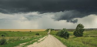Cloudy summer landscape with ground country road passing through the fields on a background of dark overcast sky. stock photography