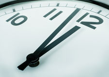 Minutes to twelve o'clock. A closeup of a clock sign minutes to twelve Royalty Free Stock Image