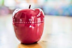 10 minutos - contador de tiempo del huevo de la cocina en la forma de Apple en la tabla de madera Imagen de archivo