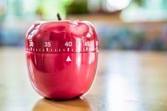 40 minutos - contador de tiempo del huevo de la cocina en la forma de Apple en la tabla de madera Imagen de archivo
