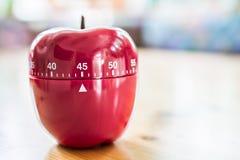 45 minutos - contador de tiempo del huevo de la cocina en la forma de Apple en la tabla de madera Imagenes de archivo
