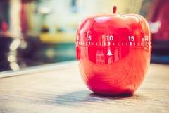 10 minutos - contador de tiempo rojo del huevo de la cocina en la forma de Apple en encimera Fotos de archivo