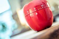 5 minutos - contador de tiempo rojo del huevo de la cocina en la forma de Apple en una tabla Fotografía de archivo libre de regalías