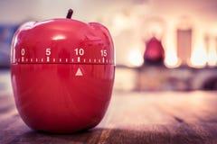 10 minutos - contador de tiempo rojo del huevo de la cocina en la forma de Apple en una tabla Imagen de archivo