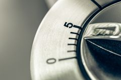 5 minutos - macro de um temporizador análogo da cozinha de Chrome na tabela de madeira Imagens de Stock