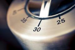 30 minutos - macro de un contador de tiempo análogo de la cocina de Chrome con el fondo oscuro Imagenes de archivo
