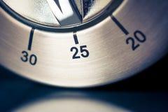 25 minutos - macro de un contador de tiempo análogo de la cocina de Chrome con el fondo y la reflexión oscuros Foto de archivo libre de regalías