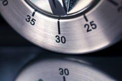30 minutos - macro de un contador de tiempo análogo de la cocina de Chrome con el fondo y la reflexión oscuros Imagen de archivo libre de regalías