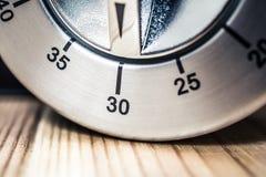 30 minutos - macro de un contador de tiempo análogo de la cocina de Chrome en la tabla de madera Imágenes de archivo libres de regalías