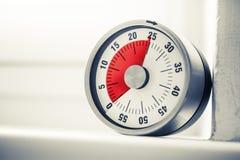 25 minutos - temporizador análogo da cozinha com Mark Placed On vermelho um peitoril da janela em cores monocromáticas imagens de stock