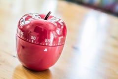 55 minutos - temporizador do ovo da cozinha na forma de Apple na tabela de madeira Imagens de Stock