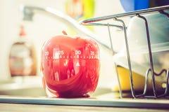 30 minutos - temporizador vermelho do ovo da cozinha em um dissipador com pratos Fotografia de Stock