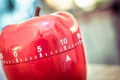 10 minutos - temporizador vermelho do ovo da cozinha na forma de Apple em uma tabela Foto de Stock Royalty Free