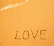 Miłość - tekst pisać ręką w piasku na plaży Fotografia Stock