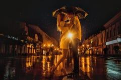 Miłość w podeszczowym, sylwetce całowanie para pod parasolem/ Zdjęcia Royalty Free