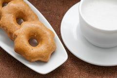 Miodowi ciastka na talerzu i filiżance mleko Zdjęcia Royalty Free