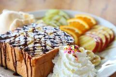 Miodowy grzanka lody z mieszanki owoc pokrajać i batożącą śmietanką słuzyć na bielu talerzu nad drewnianym stołem zdjęcia royalty free