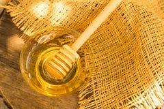 Miodowy obcieknięcie od drewnianej miodowej chochli na zamazanym tle Zdjęcia Royalty Free