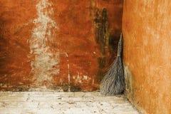 Miotła opiera przeciw ścianie w wiejskim podwórzu Fotografia Stock