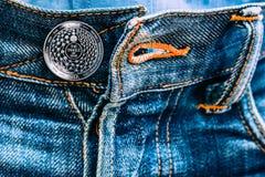 Miota-Münze anstelle der Knöpfe auf Jeans stockfoto
