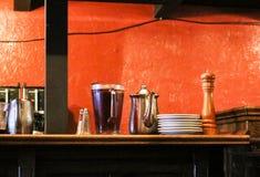 Miotacz lukrowa herbata, kawowy garnek, sól i peper na kredensie przeciw nieociosanej pomarańcze ścianie zdjęcia royalty free