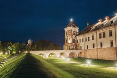 Mir, Belarus. Mir Castle Complex In Evening Illumination Lightin. G. Famous Landmark, Ancient Gothic Monument Of Feudalism Under Blue Night Sky. UNESCO Heritage stock image