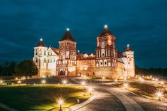 Mir, Belarus. Mir Castle Complex In Evening Illumination Lighting. Famous Landmark, Ancient Gothic Monument Of Feudalism. Under Blue Night Sky. UNESCO Hege stock photography
