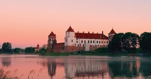 Mir, Belarus. Mir Castle Complex From Side Of Lake. Medieval Cultural Monument, UNESCO World Heritage Site. Famous. Landmark In Summer Sunny Evening Under Pink stock footage