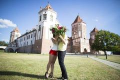 Mir, Białoruś Para całuje przed Grodowym kompleksem Mir Na słonecznym dniu z niebieskiego nieba tłem Stary średniowieczny zdjęcie stock