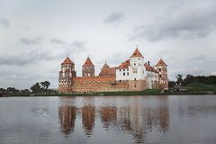 Mir castle with reflection in the water of the lake on a cloudy day royalty free stock photography